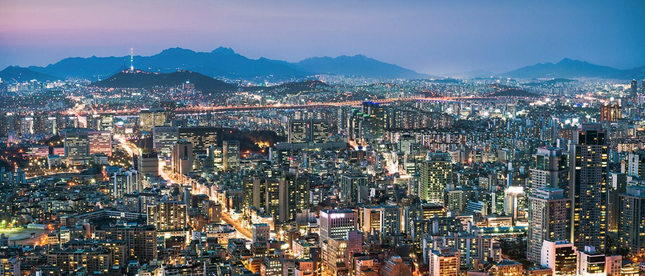 A view over South Korea's capital city, with the circular Seoul Arts Centre visible in the foreground, and N Seoul Tower on Namsan Mountain in the distance.